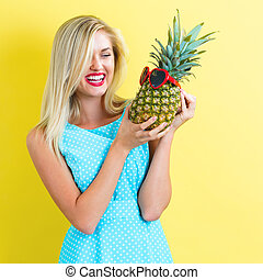 Happy young woman holding a pineapple on a yellow background