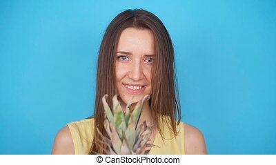 Happy young woman holding a pineapple on a blue background