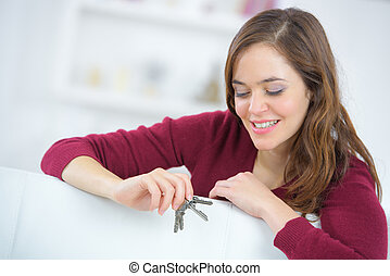 happy young woman holding a set of keys