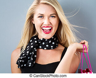 Happy young woman holding a shopping bag on a gray...