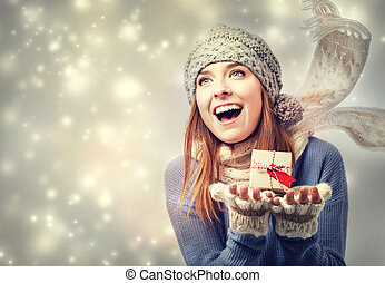 Happy young woman holding a small present box in snowy night