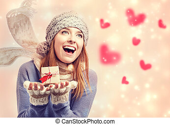 Happy young woman holding a small present box with hearts -...