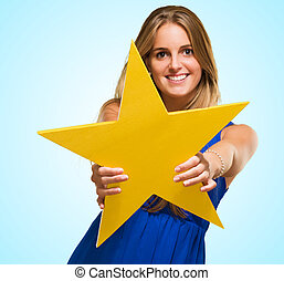 Happy Young Woman Holding A Star against a blue background
