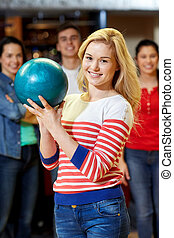 happy young woman holding ball in bowling club - people,...