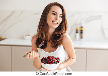 Happy young woman holding bowl with fresh berries while...