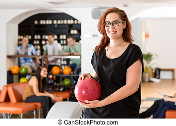 Happy Young Woman Holding Bowling Ball in Club