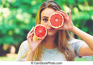 Happy young woman holding grapefruit