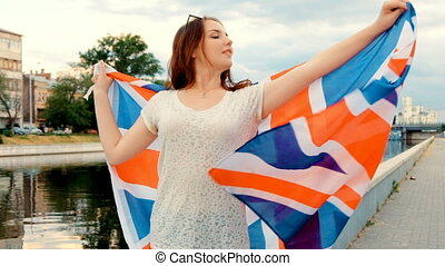 Happy young woman holding Great Britain flag.