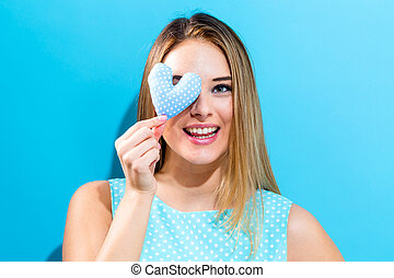 Happy young woman holding heart cushion - Happy young woman...