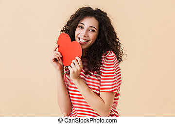 Happy young woman holding heart in hands.