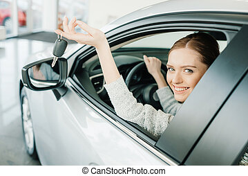 Happy young woman holding key while sitting in new car