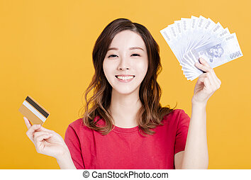 happy young woman holding money and credit card.