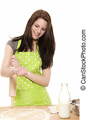 happy young woman holding rolling pin adding flour to dough on white background