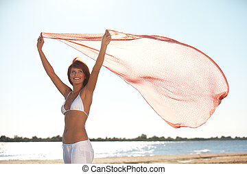 happy young woman holding scarf on beach