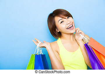 happy young  woman holding shopping bags before blue background