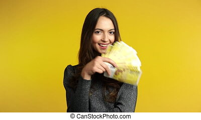 Happy young woman holding stack of money. Business, income,...