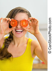 Happy young woman holding tomato slices in front of eyes