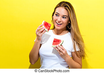 Happy young woman holding watermelons