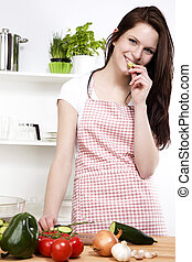 happy young woman in a kitchen nibbling on a cucumber while chopping for salad