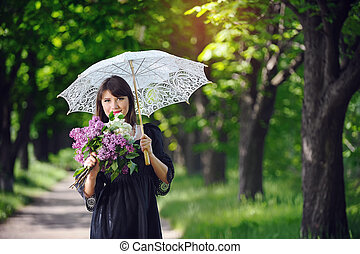 happy young woman in a spring park with an umbrella