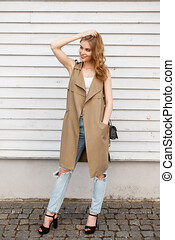 Happy young woman in a stylish summer vest in a white T-shirt in fashionable ripped jeans in black shoes with a leather handbag posing outdoors near a wooden vintage wall. Charming modern girl