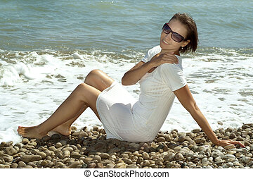 Happy young woman in a white dress on seafront