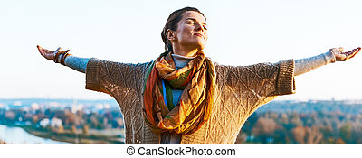 Happy young woman in autumn outdoors in evening rejoicing