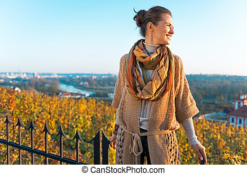 Happy young woman in autumn outdoors in evening