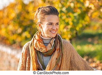 Happy young woman in autumn outdoors looking on copy space