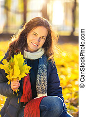 Happy young woman in autumn park