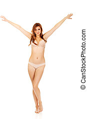 Happy young woman in beige underwear with arms up