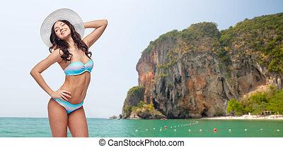 happy young woman in bikini swimsuit and sun hat - people,...