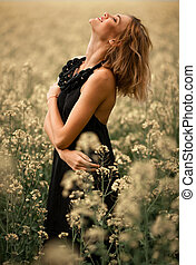 Happy young woman in black dress among flowering meadow.