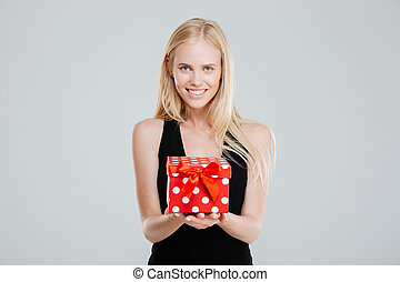 Happy young woman in black dress holding gift box