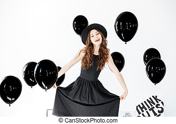 Happy young woman in black hat and dress with balloons