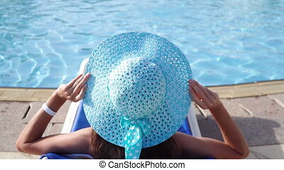 Happy young woman in blue hat lies down on lounger in hotel. Real rest by the pool. Resort on the sea. video in ProRes 1920x1080.