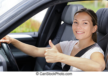 happy young woman in car with thumbs up