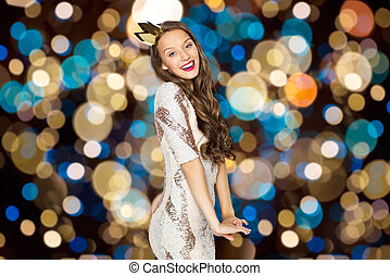 happy young woman in crown over festive lights - people,...