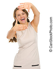 Happy young woman in dress framing with hands