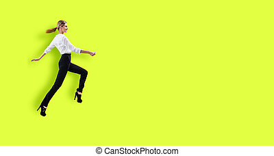 Happy young woman in formal wear jumping. Over bright yellow...