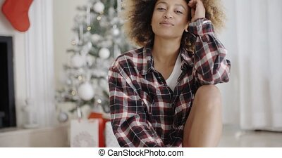 Happy young woman in front of a Christmas tree