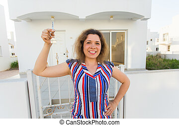 Happy young woman In Front of New Home with New House Keys
