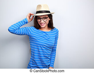 Happy young woman in glasses and straw hat looking on blue background
