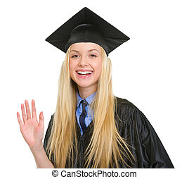 Happy young woman in graduation gown greeting