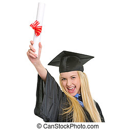 Happy young woman in graduation gown with diploma rejoicing success