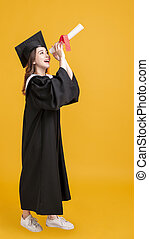 happy young woman in graduation gowns and looking through the diploma
