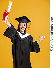 happy young woman in graduation gowns and showing the diploma