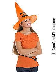 Happy young woman in Halloween hat looking on copy space