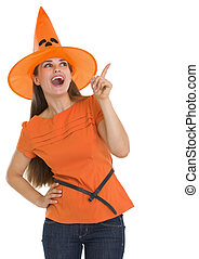 Happy young woman in Halloween hat pointing on copy space