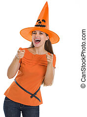 Happy young woman in Halloween hat pointing on you